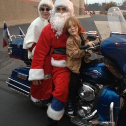 A younger Clive with Motorcycle Santa & Mrs. Claus.